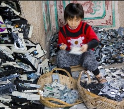 "A child in China spends the day ""preparing"" recycled electronics for salvage."